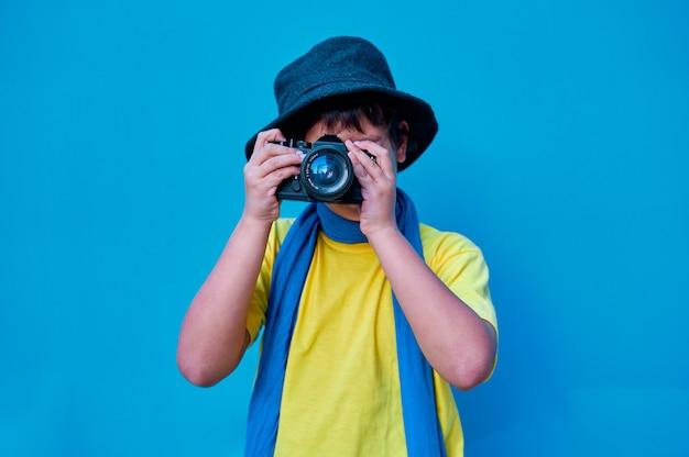 Een portret van een glimlachende jongen in geel t-shirt die een foto neemt met een analoge camera