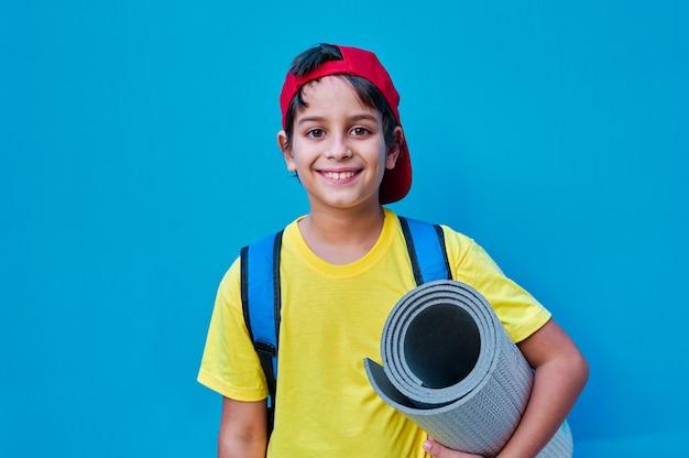 Een portret van een glimlachende jongen in geel t-shirt en rode pet met een mat en rugzak
