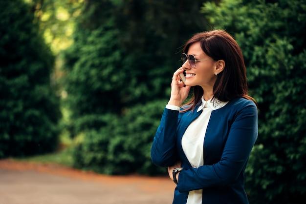 Een portret van een glimlachende mooie vrouw die op de telefoon in stadspark spreekt