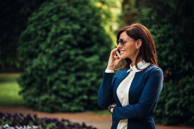 Een portret van een glimlachende mooie vrouw die op de telefoon spreekt