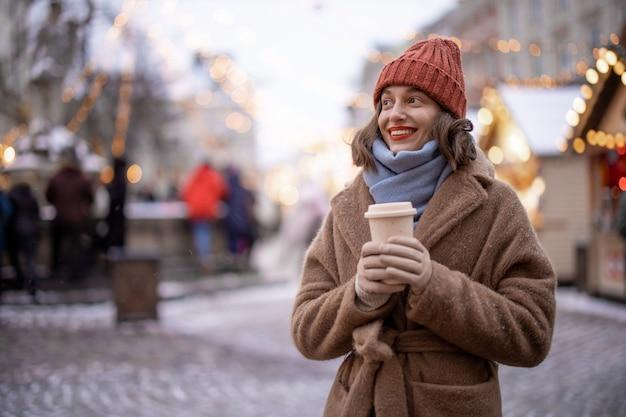 Een portret van een glimlachende vrouw met een afhaalkoffie op de achtergrond van de kerstmarkt, wandelend in de binnenstad tijdens vakanties. hoge kwaliteit foto