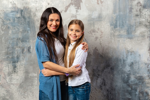 Een portret van een halve lengte van moeder en dochter die elkaar knuffelen