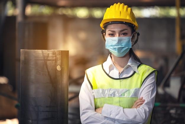Een portret van een industriële vrouweningenieur met masker die zich in een fabriek bevindt.