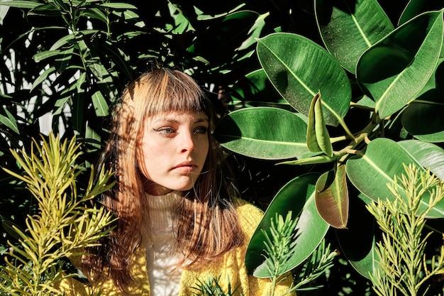 Een portret van een jong blond kaukasisch meisje met blauwe ogen tussen de groene planten van het park