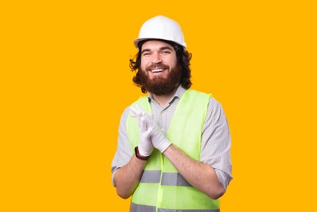 Een portret van een jonge, bebaarde architect die glimlacht, bekijkt de camera die een helm draagt, wat handschoenen en een fosforescerend vest