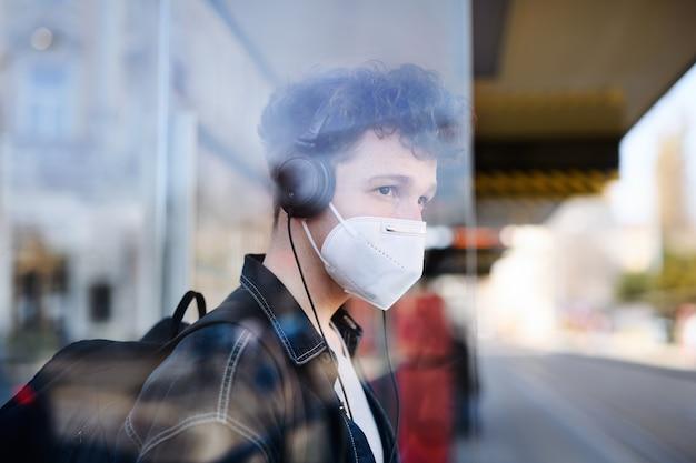 Een portret van een jonge forens die op de bushalte buiten in de stad staat, coronavirusconcept.