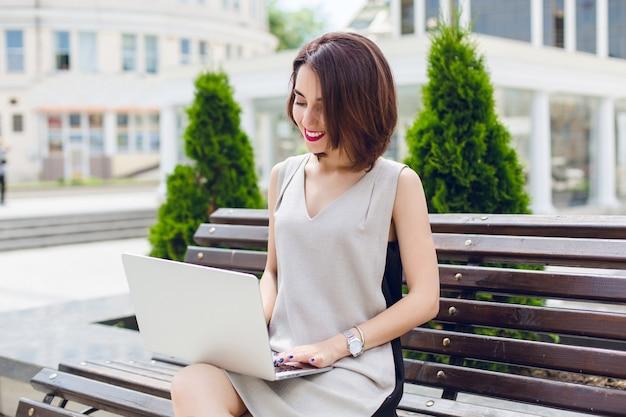 Een portret van een jonge mooie brunette meisje, zittend op de bank in de stad. ze draagt een grijze en zwarte jurk. ze typt op laptop.