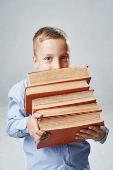 Een portret van een jongen met grote boeken