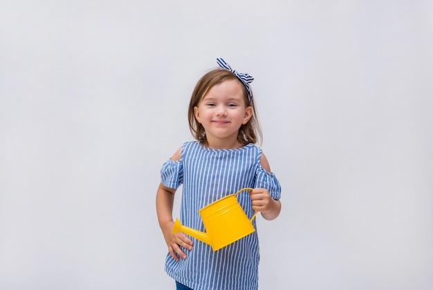 Een portret van een klein meisje die een gieter houden en op een geïsoleerd wit glimlachen
