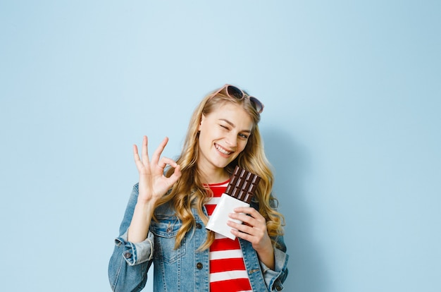 Een portret van een mooi blond meisje dat chocolade eet, is opgewonden op een blauwe achtergrond