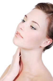 Een portret van een mooie tienervrouw met een helderwitte huid, op een witte muur.