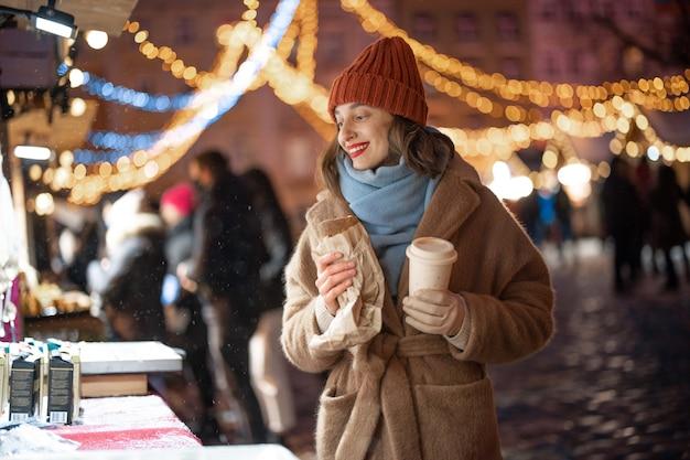 Een portret van een mooie vrouw die droomt in de buurt van de winkel en een kopje koffie houdt met afhaalmaaltijden op de kerstmarkt, wandelend in de binnenstad tijdens vakanties. hoge kwaliteit foto