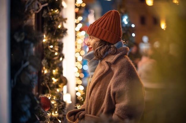 Een portret van een mooie vrouw die naar de vitrine op de kerstmarkt kijkt, tijdens de vakantie in het centrum wandelt, op zoek naar cadeaus voor de feestdagen. hoge kwaliteit foto