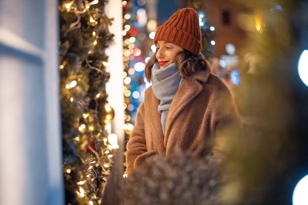 Een portret van een mooie vrouw die naar een met kerst versierde vitrine kijkt, tijdens de wintervakantie in het centrum wandelt, op zoek naar een cadeau voor vakantie. hoge kwaliteit foto