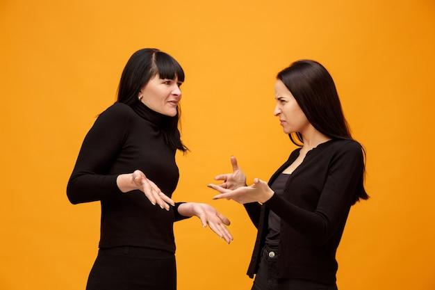 Een portret van een ongelukkige moeder en dochter in de studio op goud