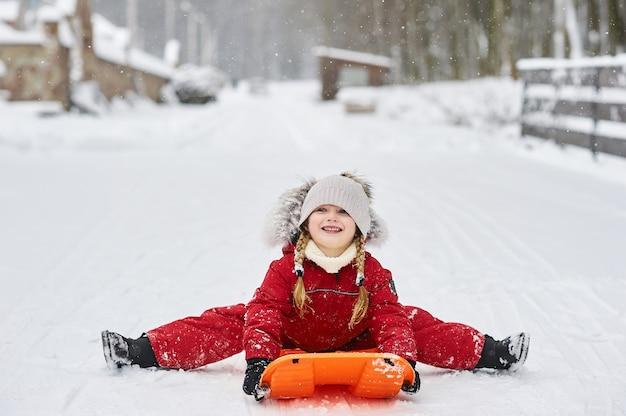 Een portret van een schattig kaukasisch kind op een slee