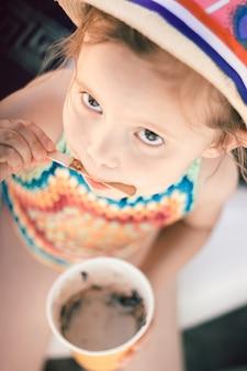 Een portret van een schattig klein meisje in een gehaakt zwempak en een hoed die gesmolten ijs uit een papieren beker eet.