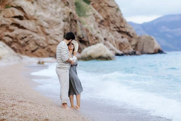 Een portret van een schattig paar in liefde zoenen en omhelzen elkaar aan de rand van het strand witj bergen op de achtergrond