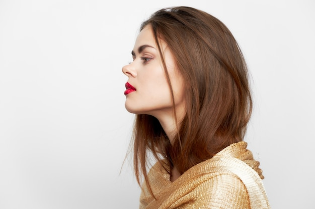 Een portret van een vrouw met een sjaal kijkt opzij rode lippen make-up geïsoleerd