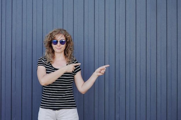 Een portret van een vrouw met zonnebril tegen een donkerblauw gestreepte muur toont haar handen opzij