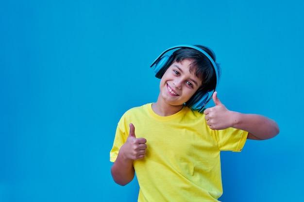 Een portret van glimlachende jongen in geel t-shirt en blauwe hoofdtelefoons die duimen opgeeft