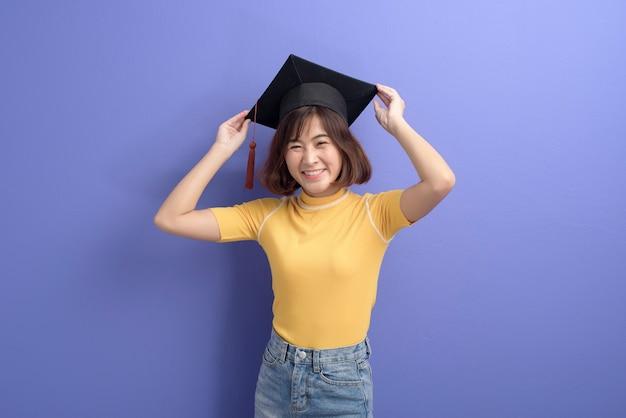 Een portret van jonge aziatische student die het afstuderen glb draagt.