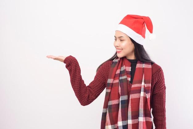 Een portret van jonge glimlachende vrouw die rode hoed van de kerstman draagt