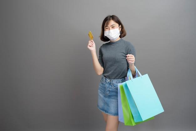Een portret van jonge mooie aziatische vrouw die chirurgische mak draagt houdt creditcard en kleurrijke die boodschappentas op grijs wordt geïsoleerd