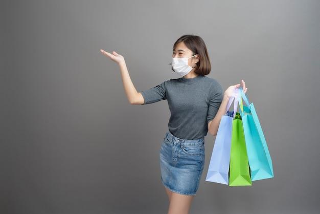 Een portret van jonge mooie aziatische vrouw die chirurgische mak draagt houdt creditcard en kleurrijke het winkelen zak