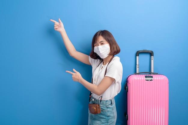 Een portret van jonge reizigersvrouw met gezichtsmasker, nieuw normaal reisconcept