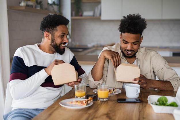 Een portret van jonge volwassen broers die thuis in de keuken zitten en afhaalmaaltijden eten.