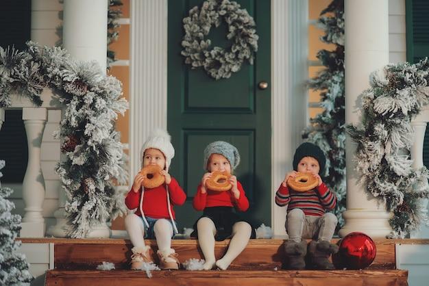 Een portret van kinderen die samen op de veranda van hun huis zitten, eat bagels. vrolijk kerstfeest gelukkig nieuwjaar. werf met een kerstboom, lichtjes en versieringen. wondertijd.