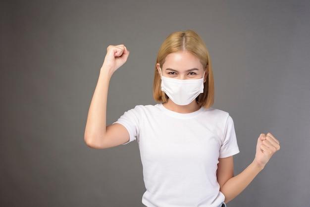 Een portret van korte blonde haarvrouw die een chirurgisch masker in studio draagt