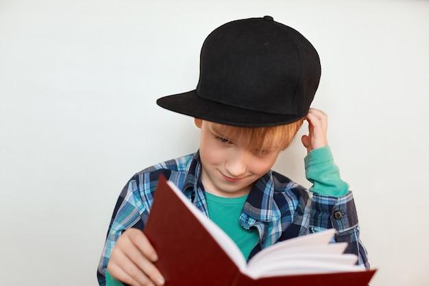 Een portret van liitle nieuwsgierig kind met blond haar in modieus glb dat groot rood boek in zijn handen houdt die zijn hoofd krabt proberend te begrijpen