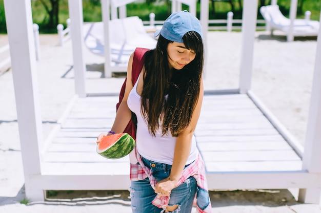 Een portret van mooi jong meisje in park met watermeloen in haar handen