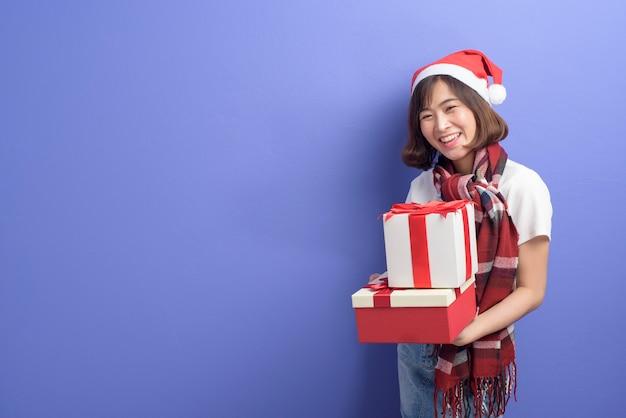Een portret van mooie vrouw die de rode doos van de de holdingsgift van de kerstmanhoed over studioachtergrond, kerstmis en nieuwjaarconcept dragen