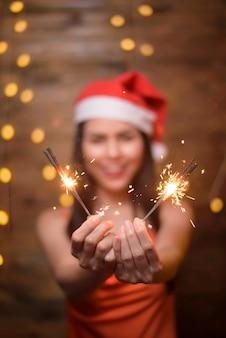 Een portret van mooie vrouw, gekleed in rode kerstman met wonderkaarsen