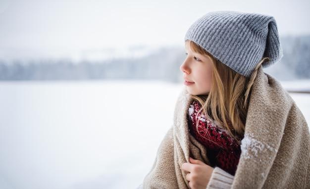 Een portret van preteen meisje buiten in de winter natuur, kopieer ruimte.