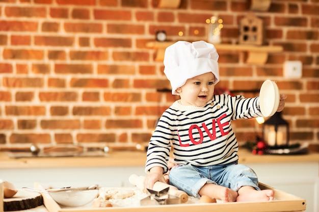 Een portret van schattige jongen gekookt en gespeeld met bloem en deeg in de keuken
