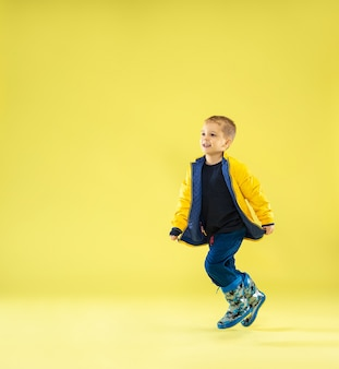 Een portret van volledige lengte van een heldere modieuze jongen in een regenjas die op geel loopt en pret heeft.