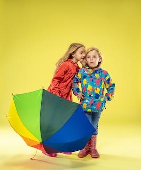 Een portret van volledige lengte van heldere modieuze meisjes in een regenjas die een paraplu van regenboogkleuren op gele studiomuur houden