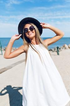Een portret van vrij blond meisje met lang haar staat op het strand bij de zee. ze lacht naar de camera.
