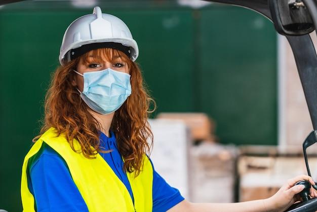Een portret vrouwelijke fabrieksarbeider in een uniform, een helm en een beschermend masker zittend in een vorkheftruck