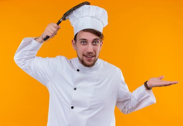 Een positieve en grappige jonge, bebaarde chef-kokmens in wit uniform die koekenpan op zijn hoofd houdt terwijl hij op een oranje muur kijkt