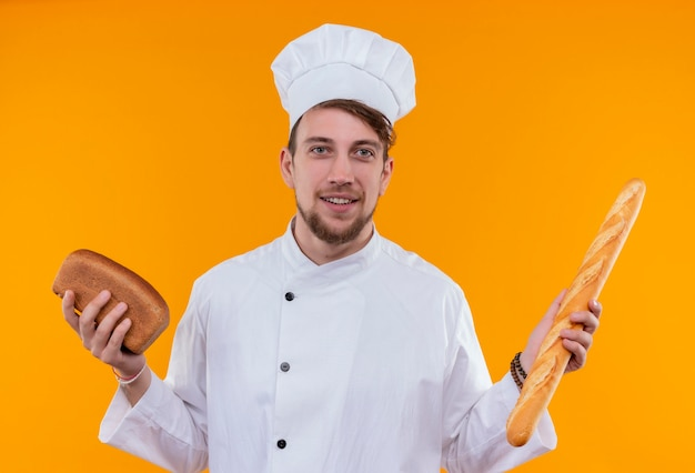 Een positieve jonge bebaarde chef-kok in wit uniform die verschillende soorten brood vasthoudt terwijl hij op een oranje muur kijkt