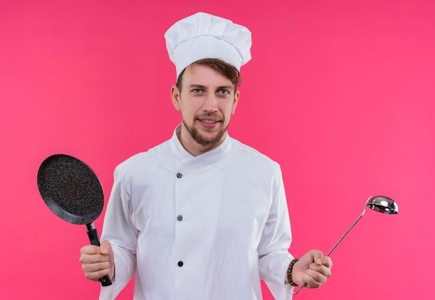 Een positieve jonge bebaarde chef-kok man in wit uniform met koekenpan en zilveren pollepel terwijl hij op een roze muur kijkt