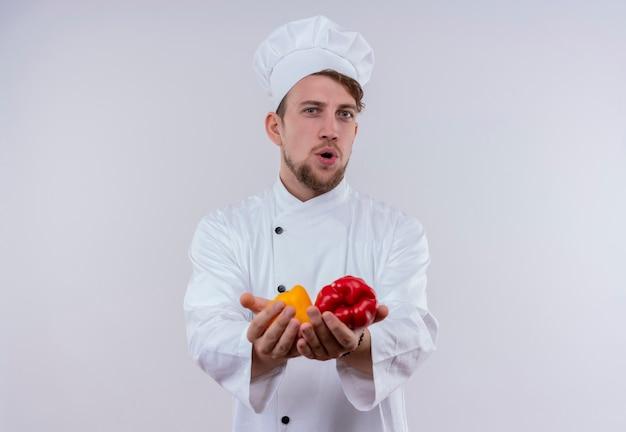 Een positieve jonge bebaarde chef-kok man met wit fornuis uniform en hoed camera kijken terwijl hij gele en rode paprika op zijn hand op een witte muur houdt