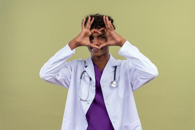 Een positieve jonge knappe donkere man met krullend haar, gekleed in een witte jas met een stethoscoop met een hartvorm teken op een groene ruimte