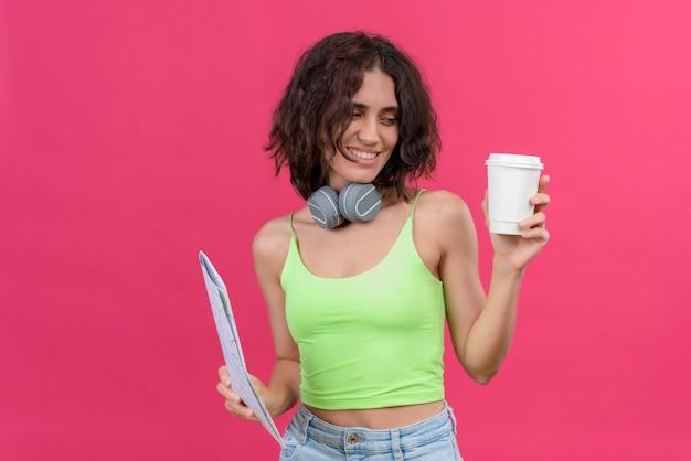 Een positieve jonge mooie vrouw met kort haar in een groene crop top in koptelefoon kijken naar een plastic kopje koffie met een kaart
