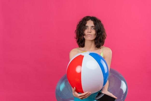 Een positieve jonge vrouw met kort haar in een groene crop top glimlachend en met opblaasbare bal